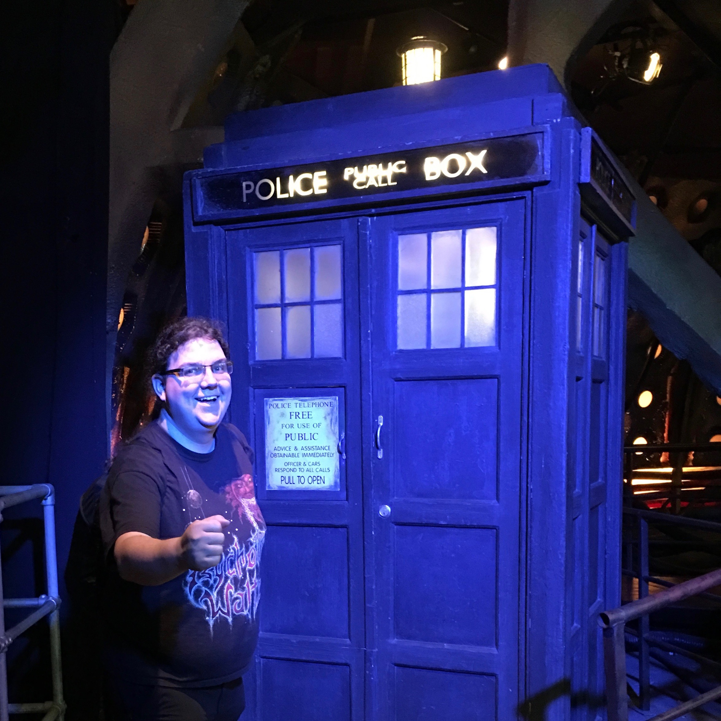 Eric Eggert, a long-haired overweight white person wearing a Metal t-shirt stands in front of an original, used on set TARDIS prop from Doctor Who in the Doctor Who Experience in Cardiff.